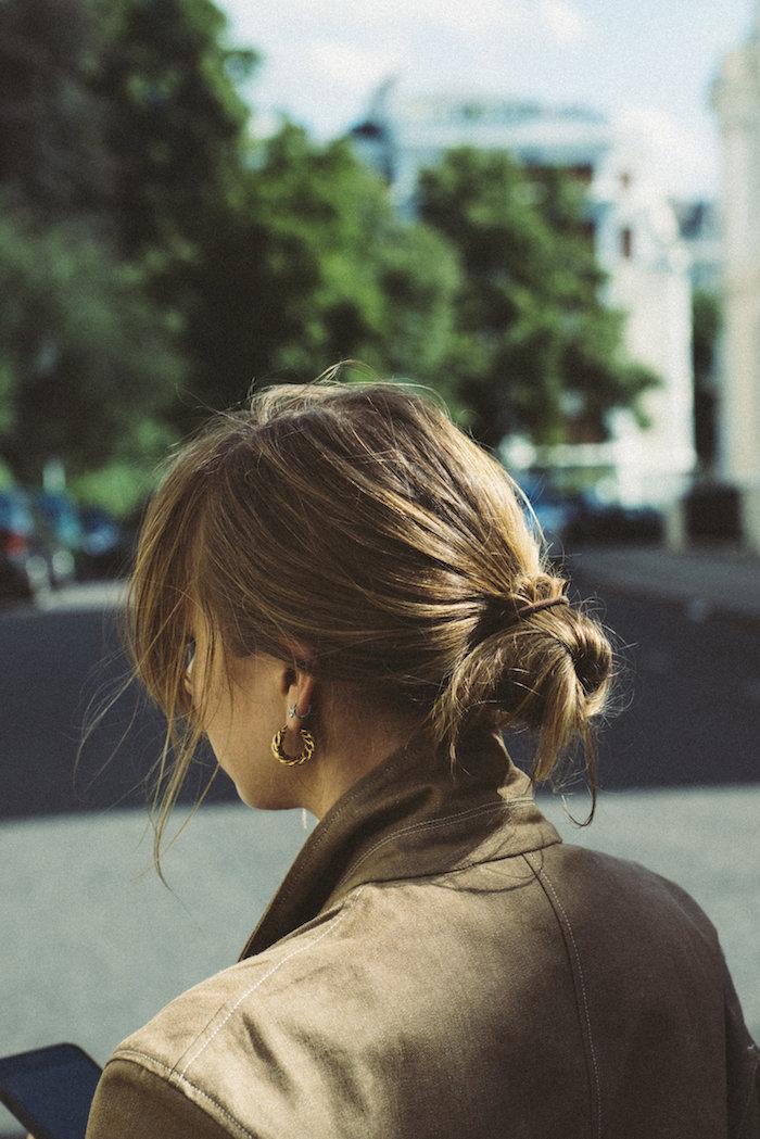 messy low bun frisuren selber machen lockerer dutt braune haare niedriger haarknoten kleine goldenen ohrringe casual street style grüne jacke