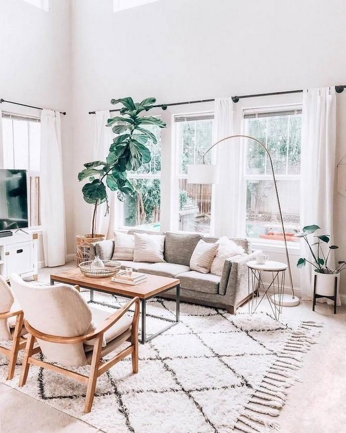 minimalistsche innenausstattung graues sofa mit kissen wohnzimmer skandinavisch einrichten ideen und inspo holzstühle mit beiger polsterung große grüne pflanze neutrale farbtöne