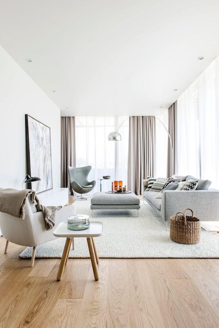 modernes skandinavisches wohnzimmer beige und graue farbtöne holzakzente große fenster mit gardinen großes gemälde an der wand skandi teppich