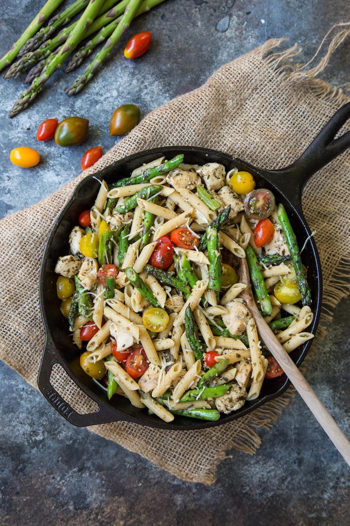 pasta mit spargel eine schwarze pfanne mit pasta kleinen roten und gelben tomaten basilikum und spargel