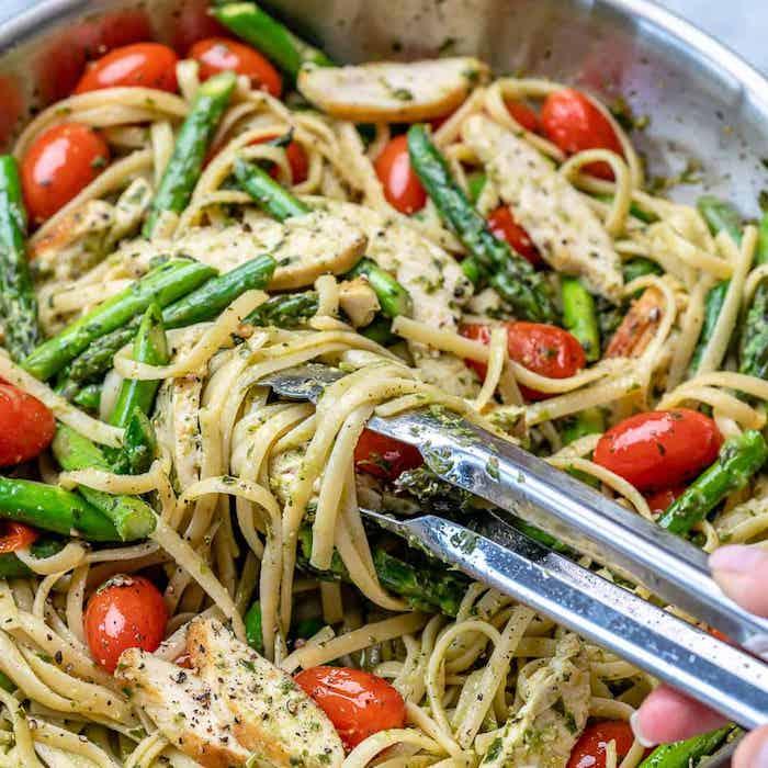 pasta mit spargeö eine pfanne mit pasta mit roten tomaten grünne spargeln und pfeffer