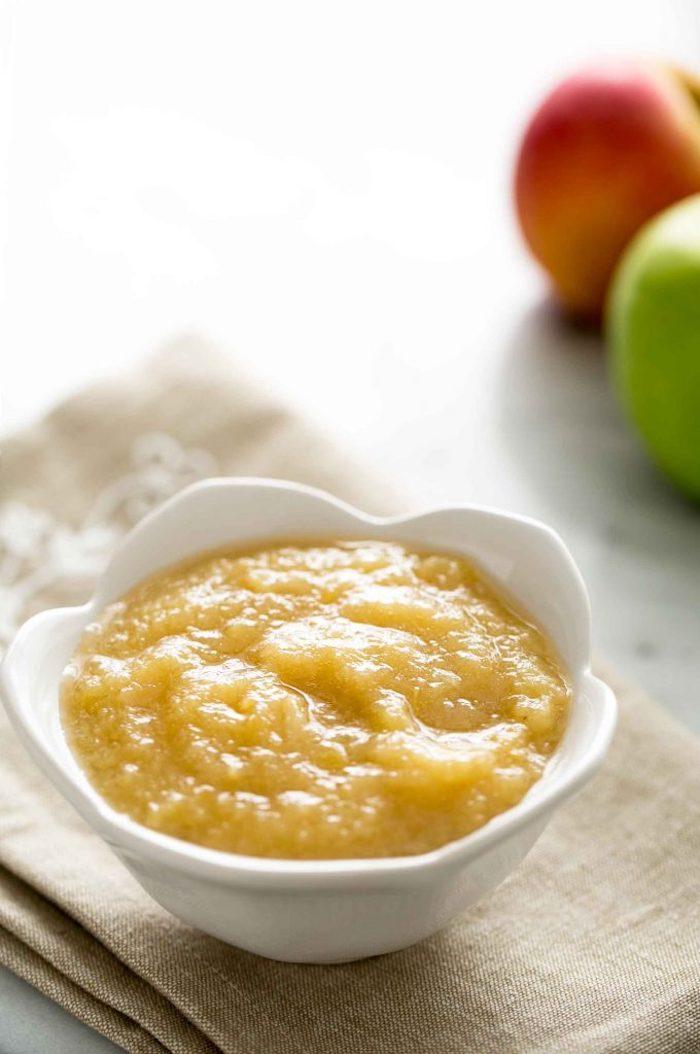 rezept für apfelmus mit einem stück zimt ein tuch und eine weiße schüssel mit apfelmus grpne und rote äpfel