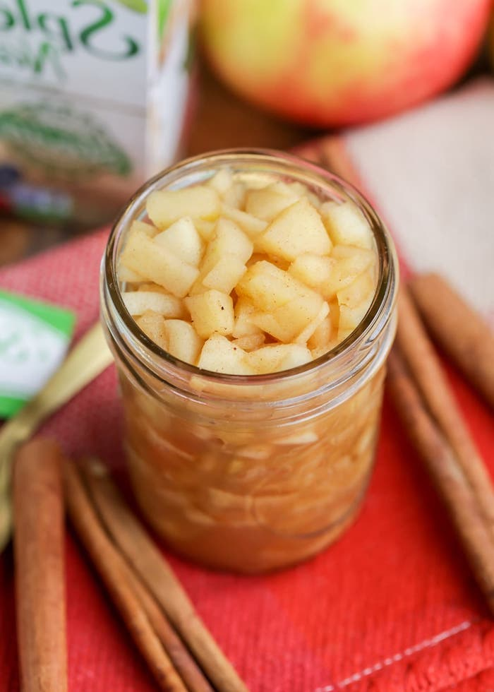 rezept für apfelmus mit einem stück zimt glas mit geschnittenen äpfeln in würfel einige braune stücke zimt rote äpfel apfelmus selber machen