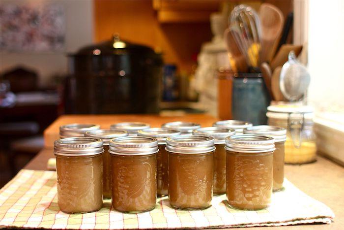 rezept für apfelmus mit einem stück zimt viele gläser mit eingekochtem apfelmus mit zimt eine küche löffel und messer ein tuch
