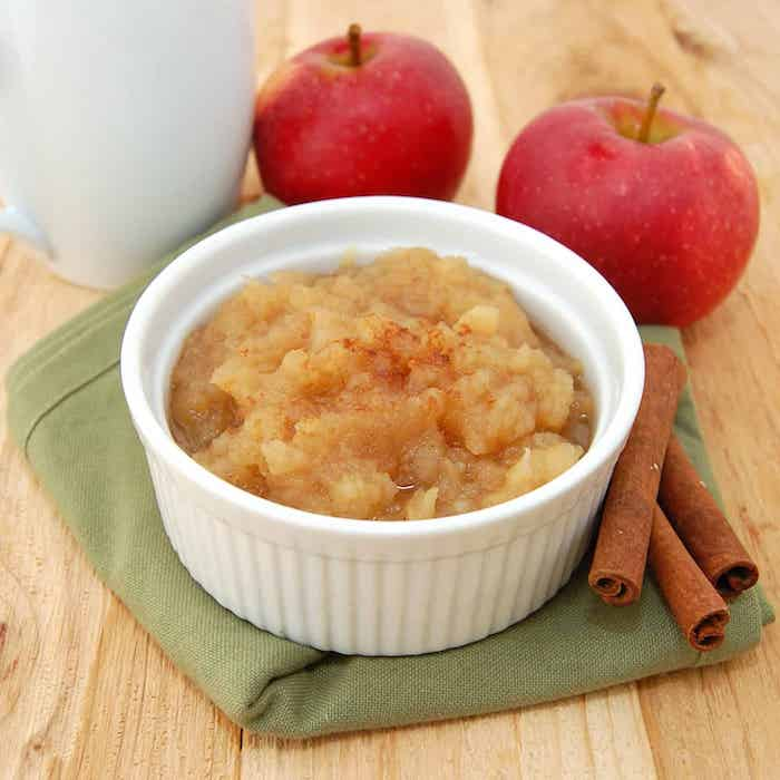 rezept für apfelmus mit einem stück zimt zwei rote äpfel und eine schüssel mit apfelmus ein grüner tuch