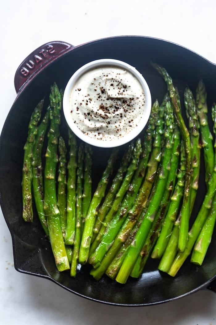 schwarzer teller mit langen grünen spargelstangen und mit weißer sauce spargel rezepte