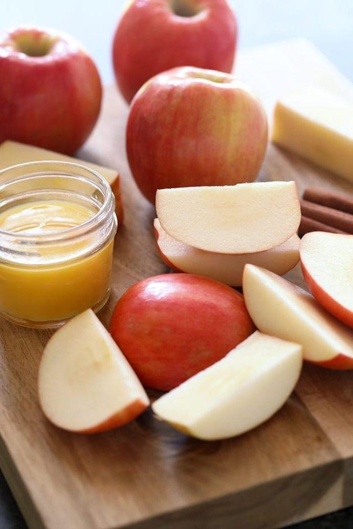 selbstgemachtes apfelmus ein holzbrett und geschnittene äpfelstücke ein glas mit zitronensaft die zutaten für ein apfelmus