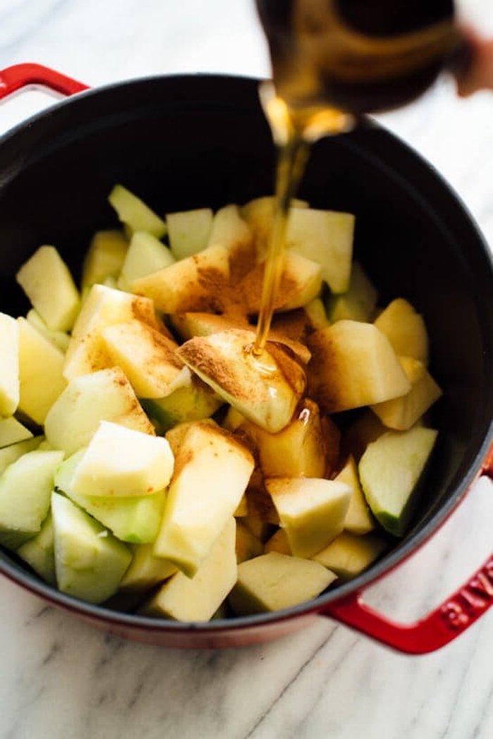 selbstgemachtes apfelmus ein topf mit zitronensaft ind geschnittene kleine apfelstücke und zimt