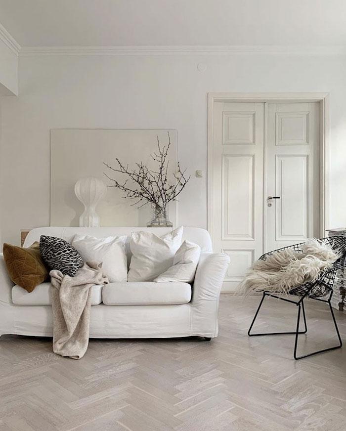 skandinavische einrichtung weiße farbtöne moderner schwarzer stuhl scandi sofa minimalistische inneneinrichtung vase mit zweigen dekoration