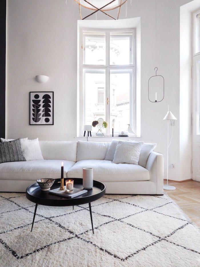skandinavischer teppich unter weißem sofa und schwarzem couchtisch mit drei beinen schwarz weißes bild dekoration ideen deko skandinavisch
