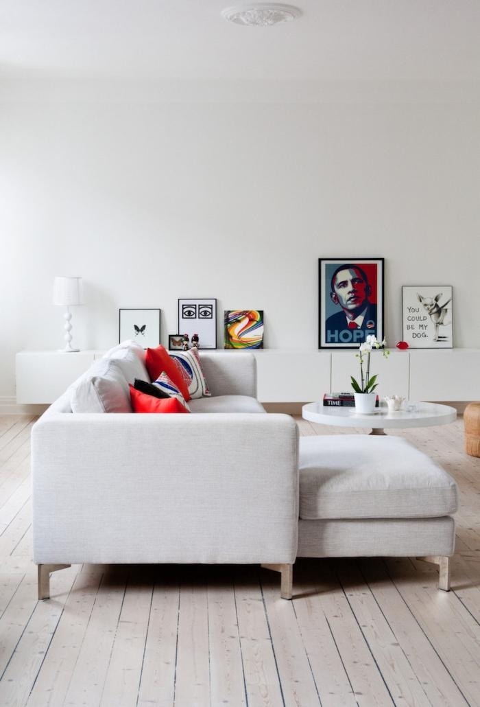 skandinavisches design mit zeitgenössischem chic ekcosofa in grau mit roten kissen bilder als dekoration runder kaffeetisch scandi sofa