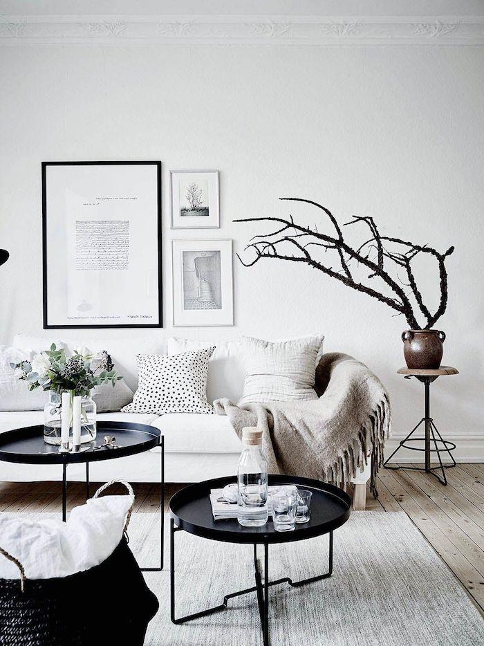 skandinavisches design zwie runde kaffeetische grauer teppich holzakzente weiße wände minimalistische bilder deko baum minimalistische einrichtung wohnzimmer