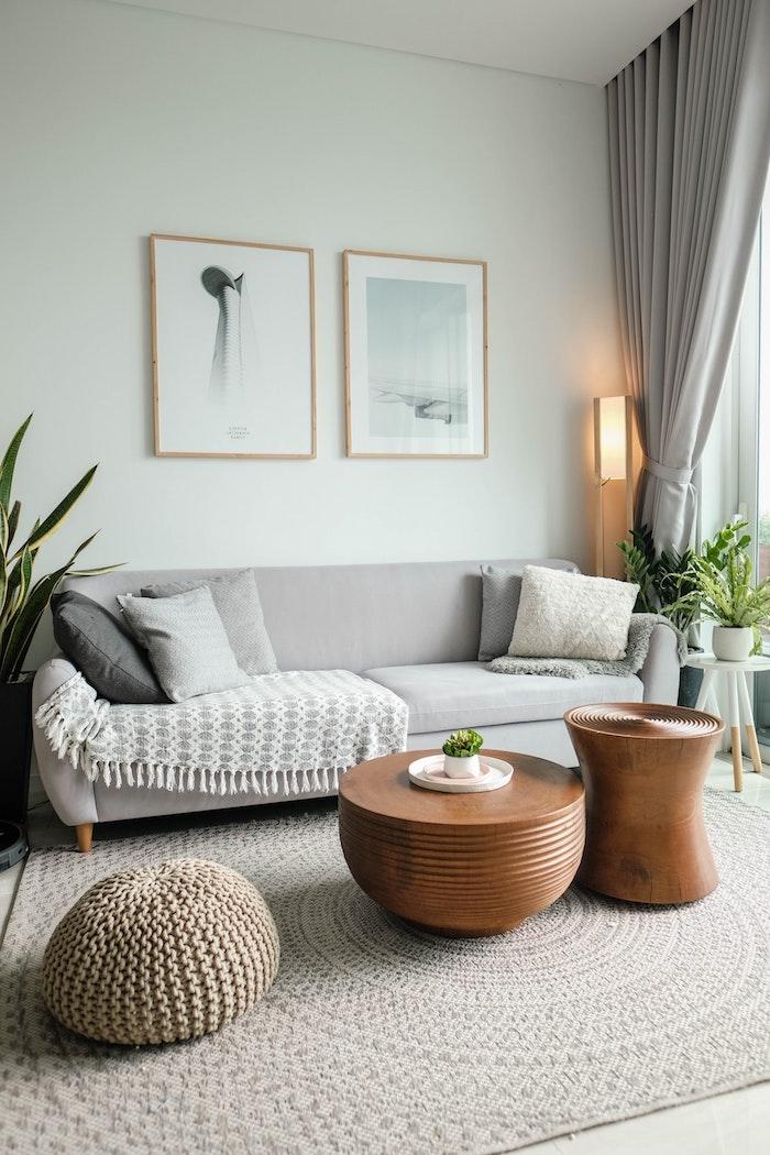 skandinavisches wohnzimmer im minimalistischen stil grauer sofa mit holzbeinen kleine kaffetische teppich in beige