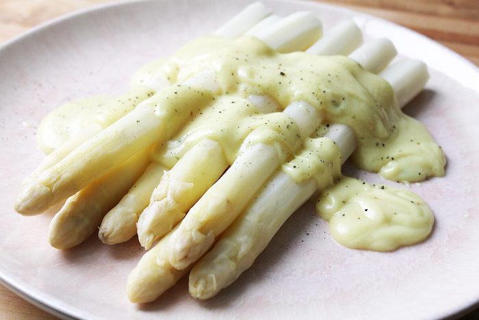 spargel rezepte ein weißer teller mit pfeffer soße hollandaise und langen geschälten weißen spargelstangen