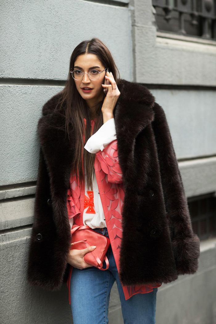 street style mailand casual outfit dunkelbrauner pelzmantel pinke mini tasche dame mit langen braunen haaren modische brillen rundes brillengestell