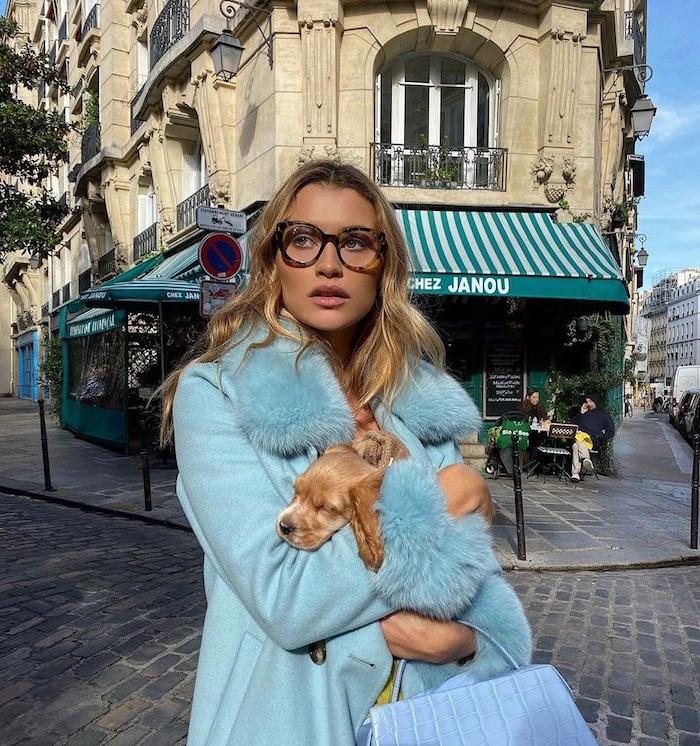 street style paris frau im eleganten hellblauen mantel lange blonde haare kleiner hund moderne brillen dicke brillengestelle damen