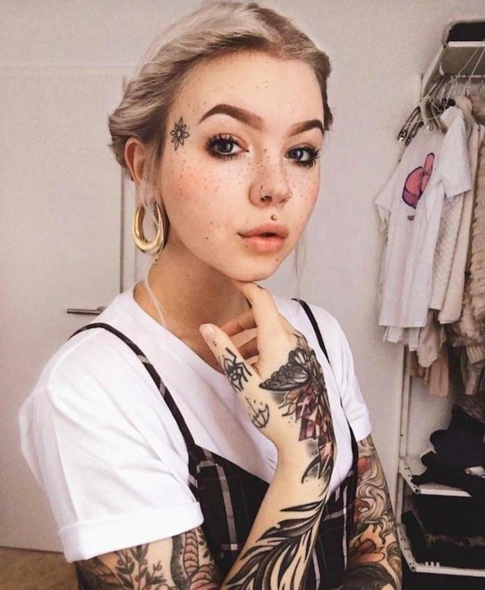 style inspiration schwarzes kleid weißes t shirt blonde haare goldenen ohrringe tattoos am arm zwei nasenringe mund piercing medusa