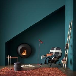 stylisches wohnzimmer einrichten ideen petrol wandfarbe grün blau flauschiger teppich braun schwarz weißer sessel runder tisch