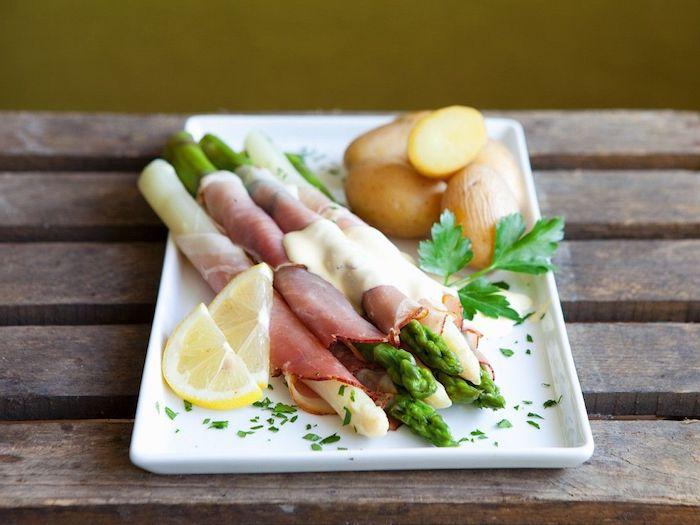 tisch aus holz spargel rezepte ein teller mit weißen spargelstangen mit schinken kartoffeln zitrone und basilikum