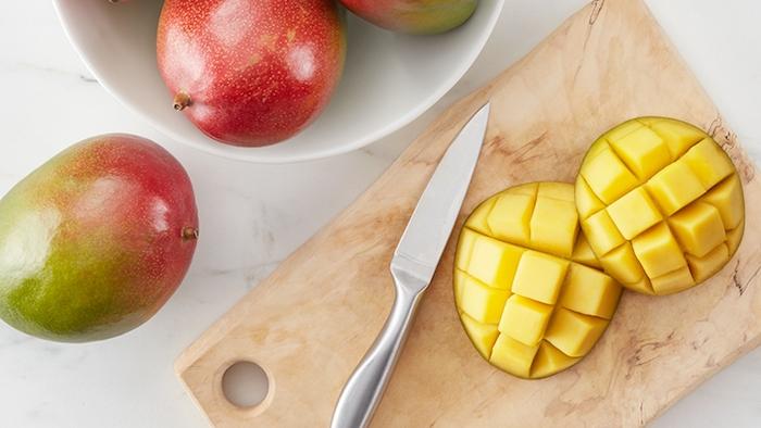 tisch und grope reife mangos ein scharfer messer und ein holzbrett zwei mango igel