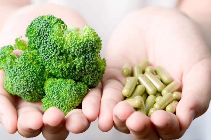 vitamin b12 zwei hände mit grünen kapseln mit nahrungsergänzungsmitteln