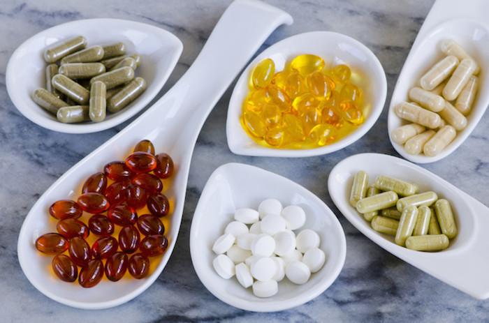 weiße löffel und kleine schüssel mit nahrungsergänzungsmitteln