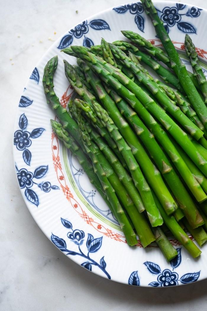weißer teller mit blauen blumen spargel rezepte viele lange geschälte grüne spargelstangen