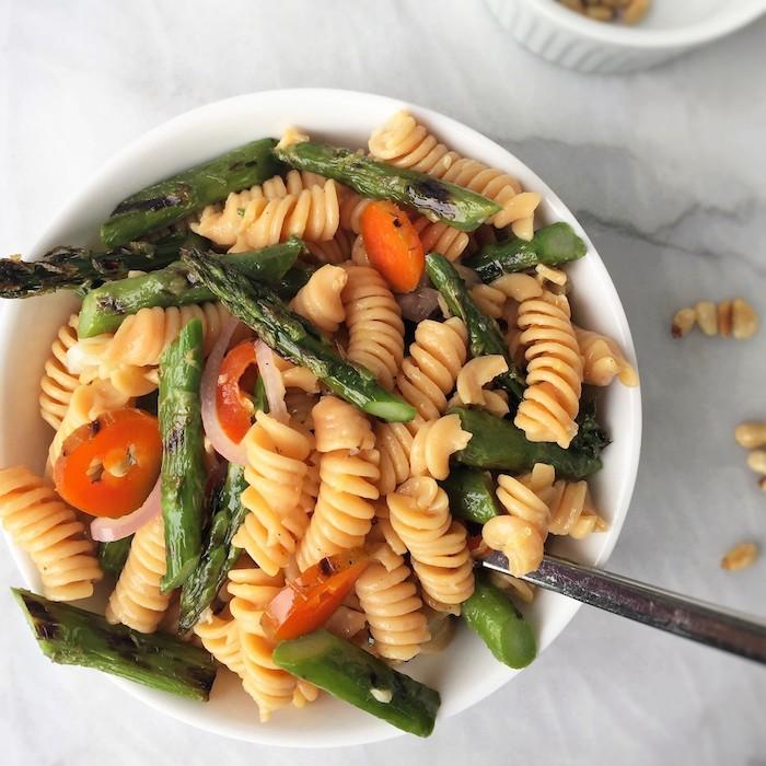 weißer teller mit pasta mit langen geschälten grünen spargeln und mit kleinen tomaten spargel rezepte ein löffel