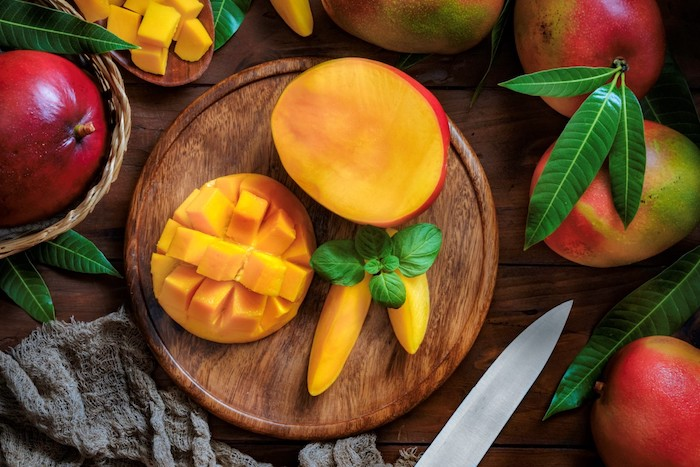 wie erkenne ich eine reife mango holzbrett mit einem messer mango und pfefferminze