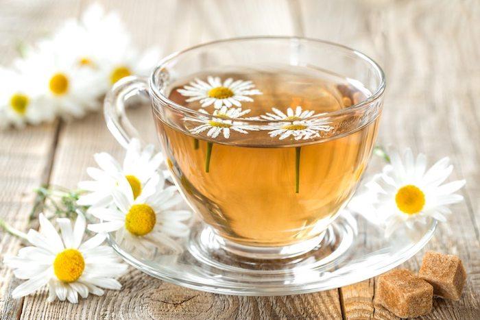 zucker und ein tisch aus holz was hilft gegen sodbrennen ein glas mit tee aus kamile