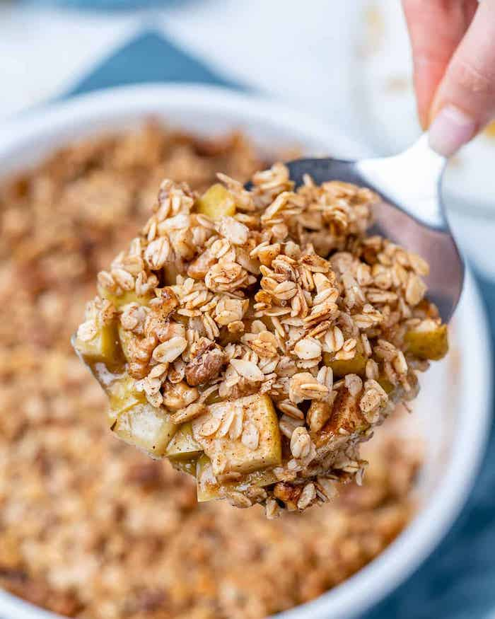 apple crumble rezept hand mit löffel und eine schlüssel mit apple crumble müsli