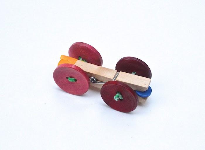 aus alt mach neu ein kleines auto aus roten und violetten knöpfen und wäscheklammern nachhaltige geschenke für kinder