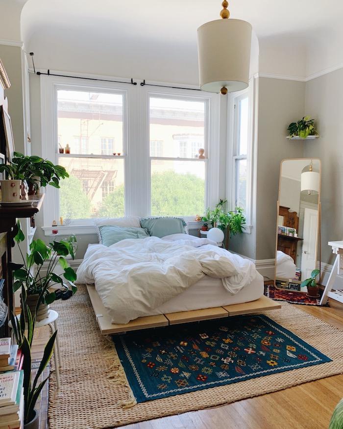 bett-aus-paletten-kleines-zimmer-geschickt-einrichten-dekoration-grüne-pflanzen-blauer-teppich-mit-blumen-weiße-bettwäsche-grüne-kissen-minimalistische-inneneinrichtung