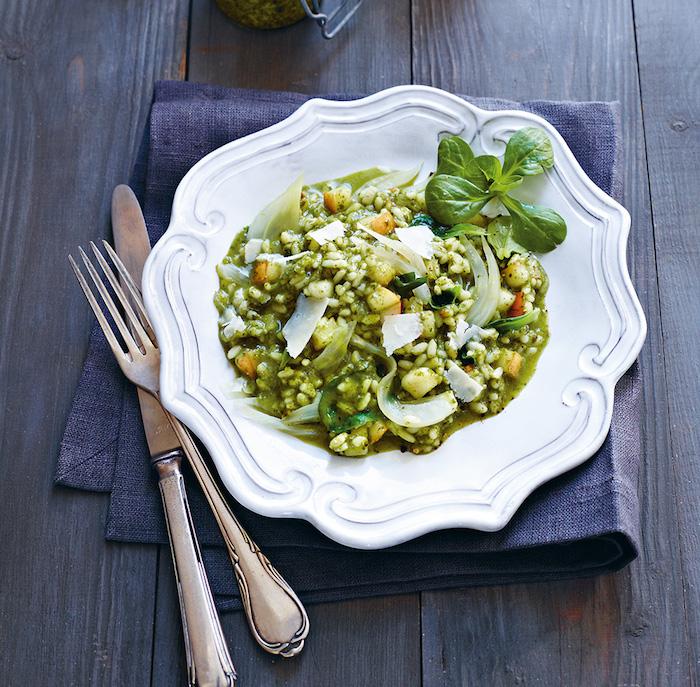 blaue decke messer und tisch aus holz ein weißer teller mit salat mit käse und blättern eines feldsalats