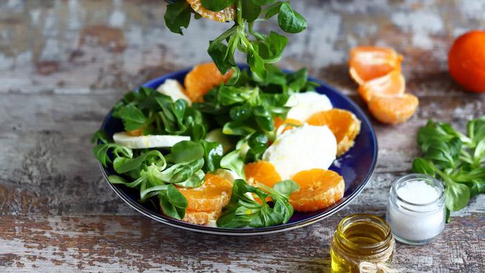 blauer teller mit kleinen orangen mandarinen dressing für feldsalat olivenöl sahne tomaten teller mit salat mit feldsalat und mandarinen