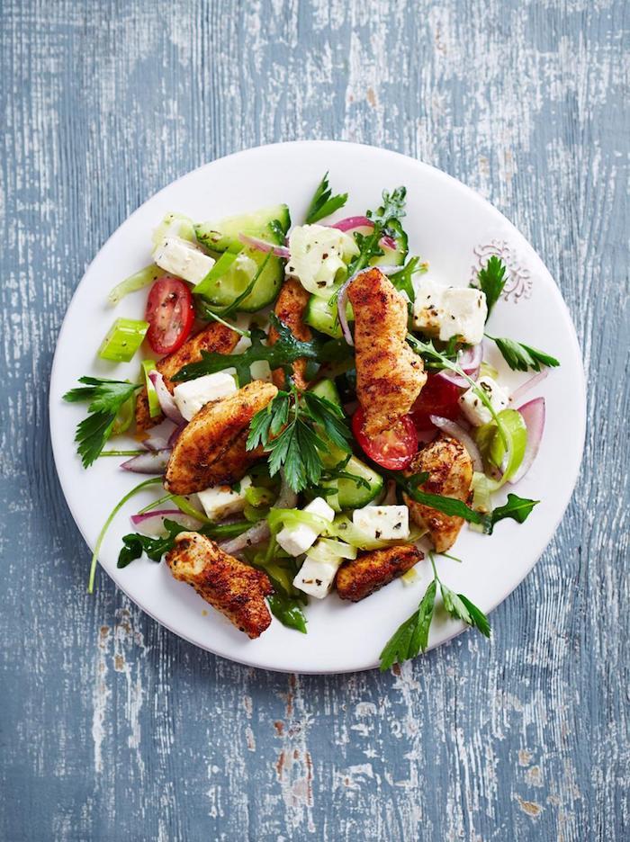 blauer tisch aus holz ein weißer teller mit salat mit grünen blättern eines feldsalats tomaten petersilie zutaten feldsalat