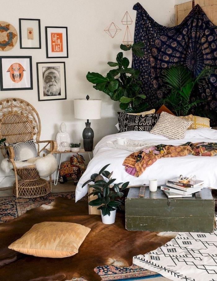 boho chic style einrichtung schlafzimmer bilder an die wand großer schwarzer wandteppich grüne pflanzen deko kissen korbstuhl vintage einrichtung