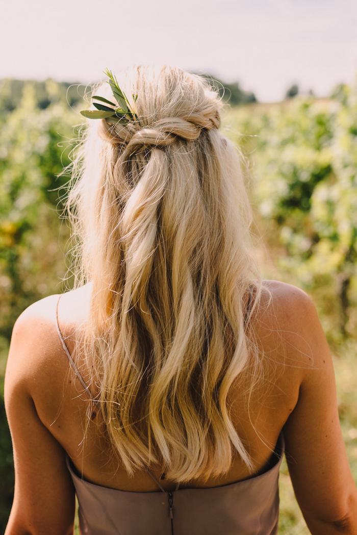 brautjunger flechtfrisuren halboffen lange blonde haare mit leichten wellen elegantes braunes kleid grünes blatt im haar accessoire boho chic hochzeit
