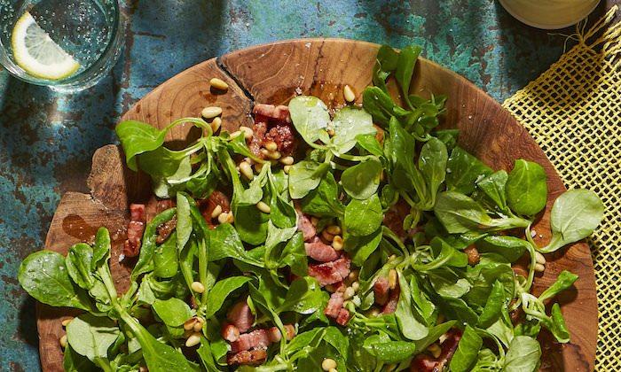 brett aus holz ein salat mit schinken nüssen und feldsalat blauer tisch aus holz ein feldsalat rezept schritt für schritt
