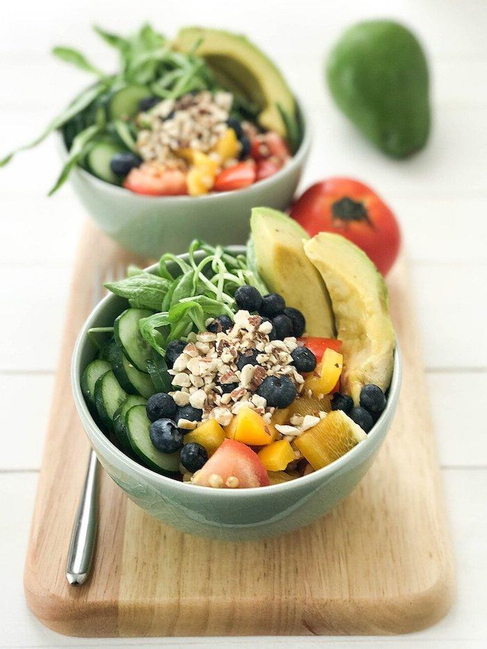 brett aus holz graue schüssel mit salat mit avocado schwarzen oliven tomaten gurken und frischen walnüssen