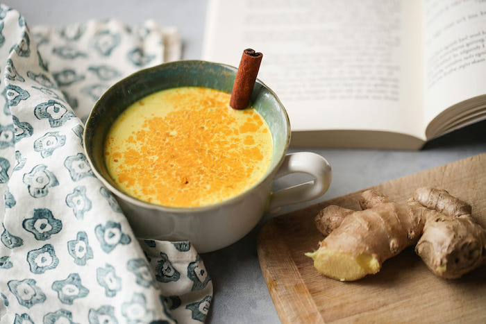 buch und ein brett aus holz eine grüne tasse mit zimt und goldener gelber milch rezept für goldene milch