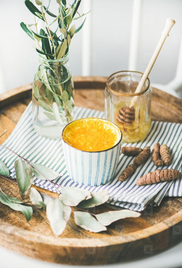 die zutaten für eine vegane goldene milch rezept. eine tasse mit goldener milch zimt und honig