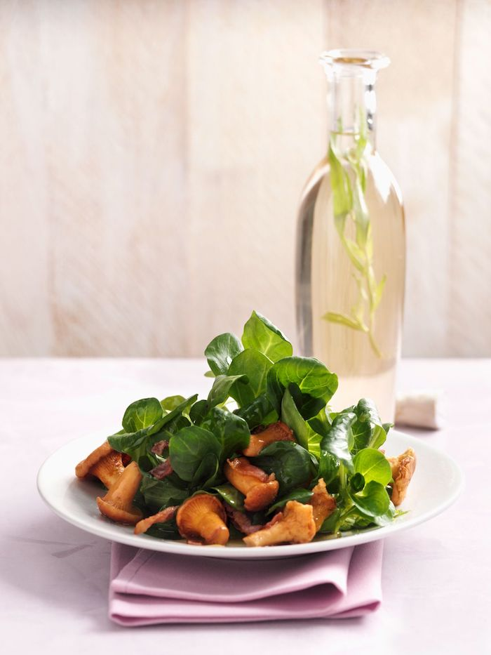 dressing für feldsalat zubereiten rezept eine pinke decke weißer teller mit salat mit feldsalat und kleinen orangen pilzen