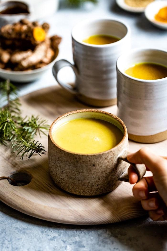 ein brett aus holz eine hand mit brauner tasse mit gelber milch rezept für goldene misch ein löffel
