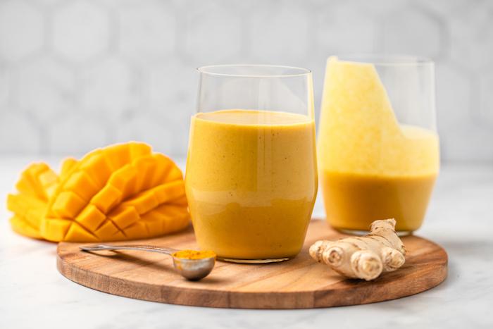 ein brett aus holz rezept für ein glas goldene milch mit inwer kurkuma und mango ein löffel