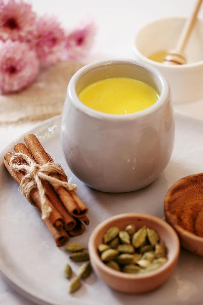 ein glas mit goldener milch weißer teller mit zimt stücken vegane goldene milch rezept pinke blumen