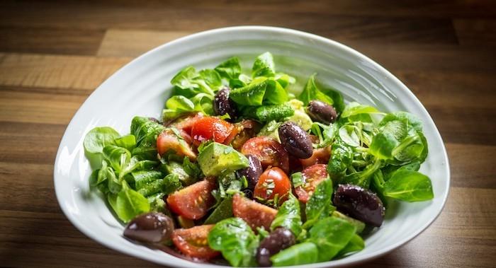 ein weißer teller mit grünen blättern eines feldsalats und schwarzen oliven und tomaten feldsalat rezepte