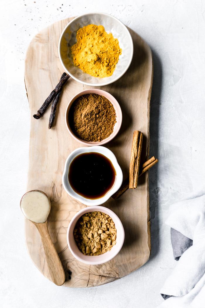 eine weiße decke und die zutaten für die vegane goldene milch rezept zimt kurkuma ingwer ein löffel