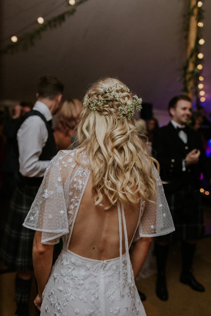 elegante hochzeit feier weiße kleid ohne rücken mit ärmeln braut mit blonden gewellten haaren mit weißen blumen hochsteckfrisuren mit locken