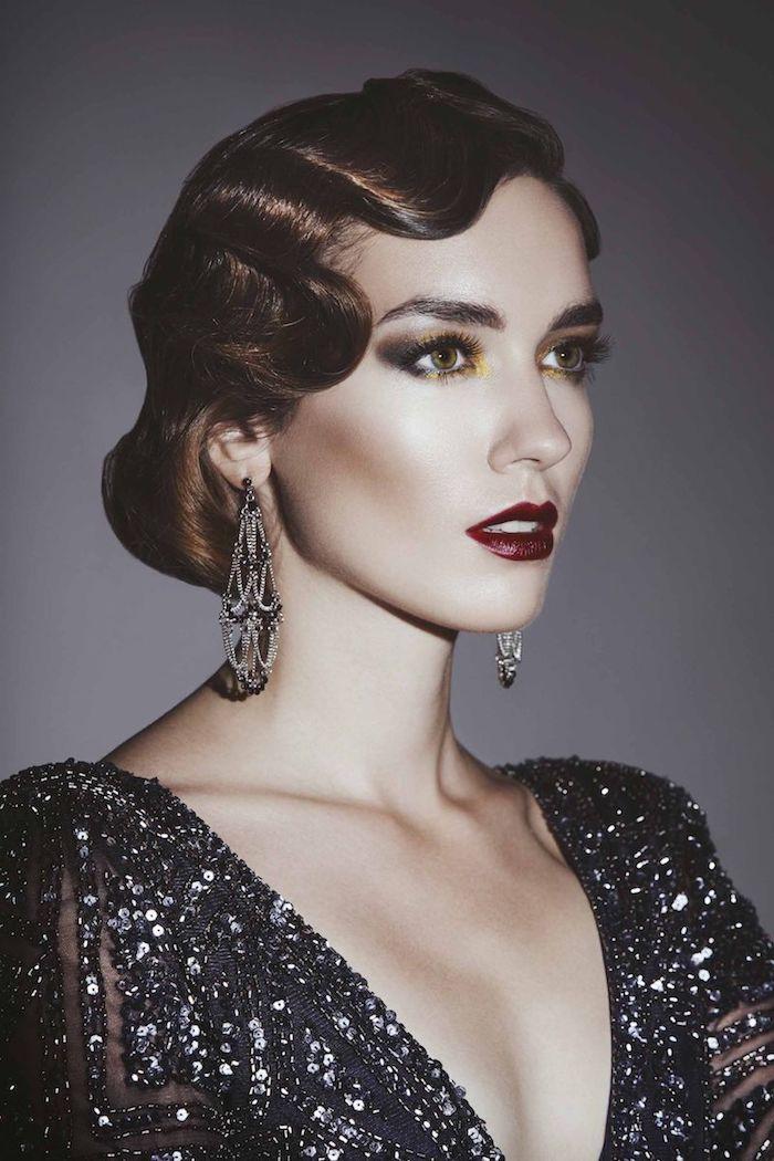 elegante retro frisur aus den 20en jahren great gatsby frau in offiziellem glänzenden kleid mit langen silbrigen ohrringen und dunkelrotem lipenstift